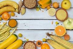 Sammansättning av gula grönsaker, bönor och frukter - banan, havre, citron, plommon, aprikos, peppar, zucchini, tomat, sparrisbön royaltyfri foto