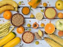 Sammansättning av gula grönsaker, bönor och frukter - banan, havre, citron, plommon, aprikos, peppar, zucchini, tomat, sparrisbön royaltyfria bilder