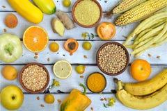 Sammansättning av gula grönsaker, bönor och frukter - banan, havre, citron, plommon, aprikos, peppar, zucchini, tomat, sparrisbön arkivfoton