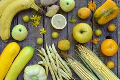 Sammansättning av gula grönsaker och frukter - banan, havre, citron, plommon, aprikos, peppar, zucchini, tomat, sparrisbönor, gin fotografering för bildbyråer