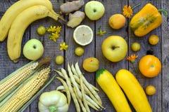 Sammansättning av gula grönsaker och frukter - banan, havre, citron, plommon, aprikos, peppar, zucchini, tomat, sparrisbönor, gin arkivbild