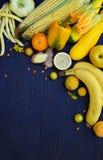 Sammansättning av gula grönsaker och frukter - banan, havre, citron, plommon, aprikos, peppar, zucchini, tomat, sparrisbönor, gin arkivfoto