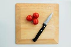 Sammansättning av körsbärsröda tomater och kniven arkivbilder