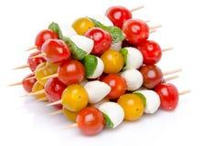Sammansättning av körsbärsröda tomater och mozzarellaen på steknålar Royaltyfri Fotografi