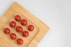 Sammansättning av körsbärsröda tomater på plattan royaltyfria bilder