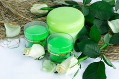 Sammansättning av kosmetiska omsorgflaskor med rosor Arkivbild