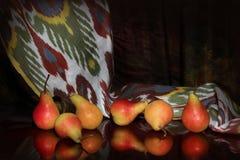 Sammansättning av mogna päron och uzbekiska traditionella ikatadrass Royaltyfria Bilder