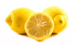Sammansättning av nya och klippta citroner på en vit bakgrund Arkivfoto