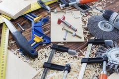 Sammansättning av olika funktionsdugliga hjälpmedel mejslar, borrar, skruvar, kniven och chiper på skrivbordet i det wood seminar Arkivbilder