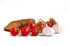 Sammansättning av skivor för svart bröd, grupp av körsbärsröda tomater, gar Royaltyfri Bild
