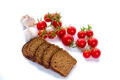 Sammansättning av skivor för svart bröd, körsbärsröda tomater och vitlök Fotografering för Bildbyråer