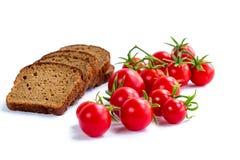 Sammansättning av skivor för svart bröd och grupp av körsbärsröda tomater Royaltyfri Bild