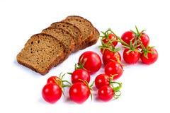 Sammansättning av skivor för svart bröd och körsbärsröda tomater Arkivfoton