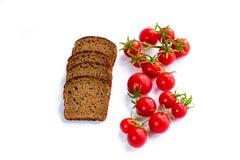 Sammansättning av svart bröd och grupp av körsbärsröda tomater Royaltyfri Bild