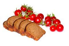 Sammansättning av svart bröd och körsbärsröda tomater Fotografering för Bildbyråer