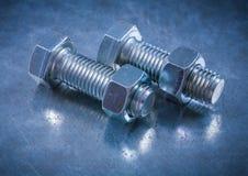 Sammansättning av trådda bultar och konstruktionsmuttrar på metalliskt Royaltyfri Fotografi