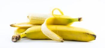Sammansättning av tre bananer en av dem skalas på en vit bakgrund Royaltyfri Fotografi