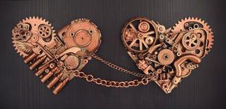 Sammansättning av två kedjade fast hjärtor som samlades från olika mekaniska delar Arkivbild