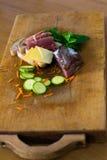 Sammansättning av två skivor av bröd, salami, ost, zucchinier, spenat och stycken av moroten Royaltyfri Foto