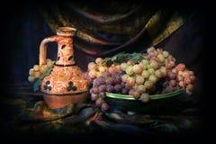 Sammansättning av uzbekisk traditionell keramisk vattenvesel, den keramiska maträtten och druvor Royaltyfri Foto
