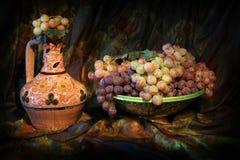 Sammansättning av uzbekisk traditionell keramisk vattenvesel, den keramiska maträtten och druvor Royaltyfri Bild