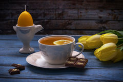 sammansättning easter Citronte, choklad, gula tulpan, stearinljus i äggform på tappningträbakgrund Arkivbild