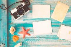Sammansättning för bästa sikt - fotoramar för tomt papper med sjöstjärnan, skal, korall och objekt på trätabellen Arkivbilder