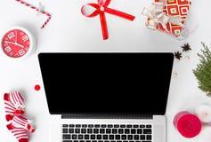 Sammansättning för jul för bärbar datordator Jul gåva och julgarneringar på vit bakgrund Lekmanna- bästa sikt för lägenhet Arkivfoto