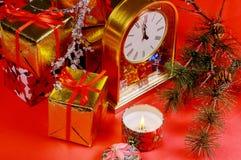 Sammansättning för jul eller för nytt år med den röda bakgrundsstearinljuset Klocka för tolv o Begrepp för nytt år s royaltyfri bild