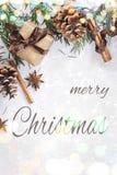 Sammansättning för jul och för nytt år Gåvaasken med bandet, gran förgrena sig med kottar, stjärnaanis, kanel på vit bakgrund royaltyfri bild