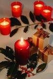 Sammansättning för jul och för nytt år Litstearinljus, gåvaaskar och filial av järnek royaltyfri bild