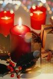 Sammansättning för jul och för nytt år Litstearinljus, gåvaaskar och filial av järnek arkivfoton