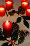 Sammansättning för jul och för nytt år Litstearinljus, grankottar och filial av järnek arkivbild