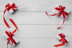 Sammansättning för julferiebakgrund Julgåvor med det röda bandet på den vita trätabellen Kort för Xmas och för lyckligt nytt år royaltyfri fotografi