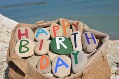 Sammansättning för lycklig födelsedag av stenbokstäver i en påse Arkivfoton