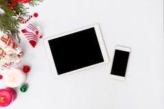 Sammansättning för minnestavlasmartphonejul granfilialer, kottar och julgarneringar på vit bakgrund Lekmanna- bästa sikt för läge royaltyfri foto
