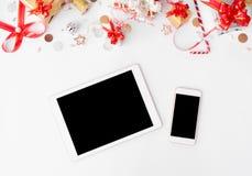 Sammansättning för minnestavlasmartphonejul Julgåvor och garneringar på vit bakgrund Lekmanna- bästa sikt för lägenhet Royaltyfri Foto