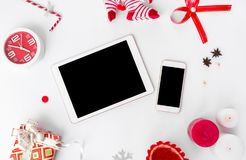 Sammansättning för minnestavlasmartphonejul kottar och julgarneringar på vit bakgrund Lekmanna- bästa sikt för lägenhet royaltyfri bild