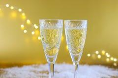 Sammansättning för ` s för nytt år: Två exponeringsglas med champagne på en guldbac Arkivfoton