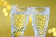 Sammansättning för ` s för nytt år: Två exponeringsglas med champagne på en guldbac Royaltyfria Bilder