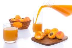Sammansättning med aprikosfruktsaft hällde in i ett exponeringsglas Royaltyfri Bild