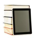 Sammansättning med böcker och minnestavladatoren på vit Arkivbild