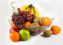 Sammansättning med blandade frukter i korg på vit Arkivfoto