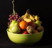 Sammansättning med blandade frukter i stor bunke på svart Arkivfoton