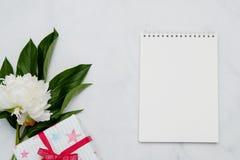 Sammansättning med blommor och anteckningsboken på vit bakgrund Åtlöje upp för din design Lekmanna- lägenhet royaltyfri bild