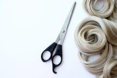 Sammansättning med blont hår, sax och utrymme för text på en kulör bakgrund Friseringservice För affärskort eller stolpe royaltyfri bild