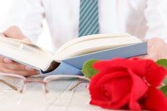 Sammansättning med boken, exponeringsglas och den röda rosen Arkivbilder