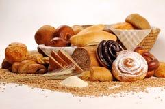 Sammansättning med bröd och rullar i vide- korg, kombination av söta bakelser för bageri eller marknad med vete Arkivbild