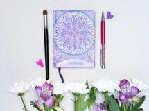 Sammansättning med den makeupborsten, pennan, arbetsboken och blommor på grå bakgrund royaltyfri fotografi
