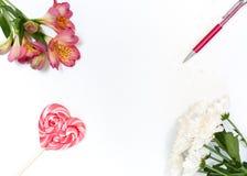Sammansättning med den makeupskönhetsmedel, pennan, kortet och blommor på vit bakgrund fotografering för bildbyråer